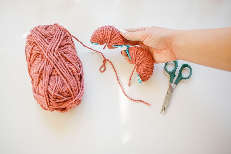 Wrap yarn around each side of pompom maker